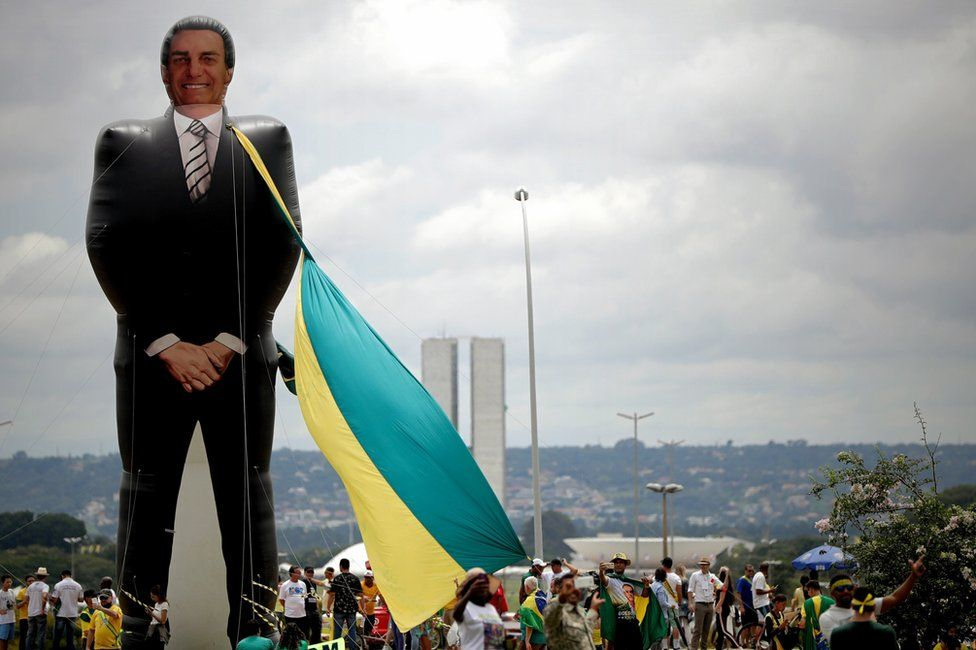 Sympathisers of Brazilian President-elect, Jair Bolsonaro, walk past a giant figure of the future president before the beginning of the inauguration ceremony, in Brasilia, Brazil, 01 January 2019