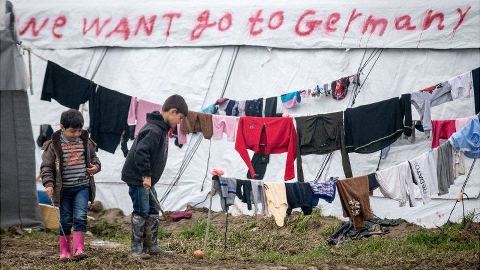 Children play in front of washing drying at the Idomeni refugee camp on the Greek Macedonia border on March 17, 2016 in Idomeni, Greece