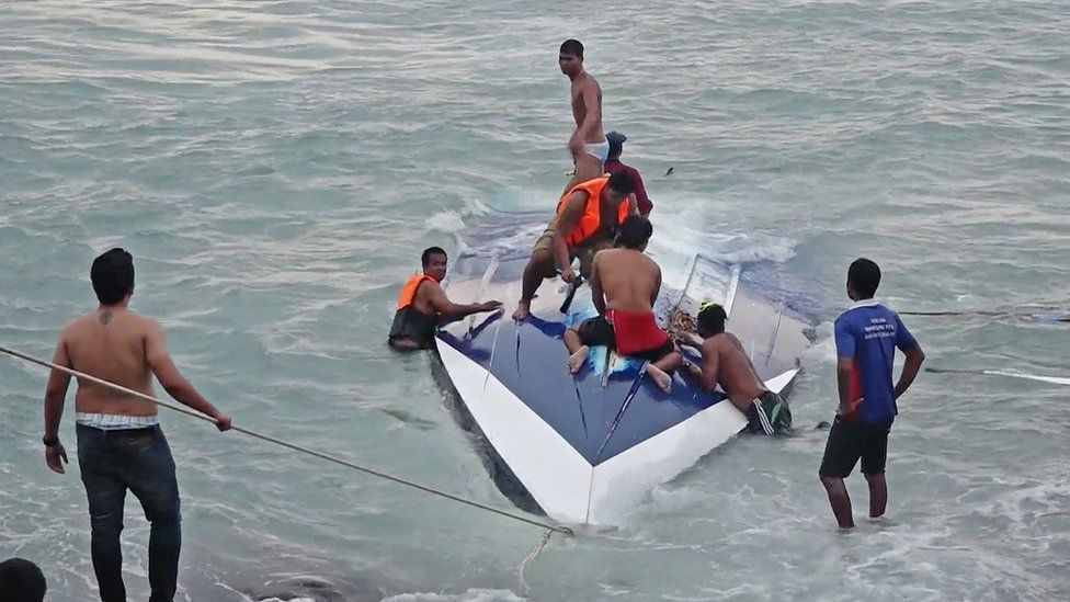 Rescuers on top of the capsized boat