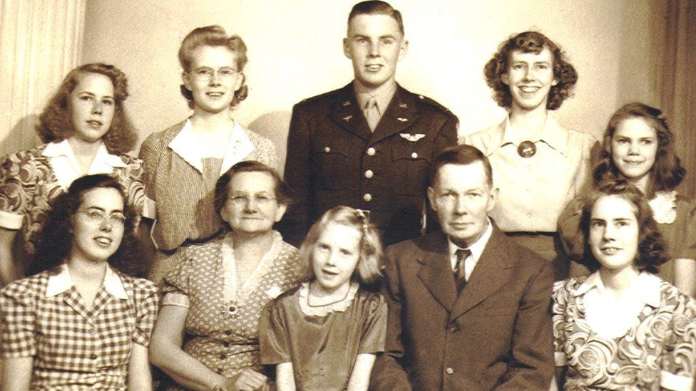 John Walker surrounded by seven of his eight sisters and his parents