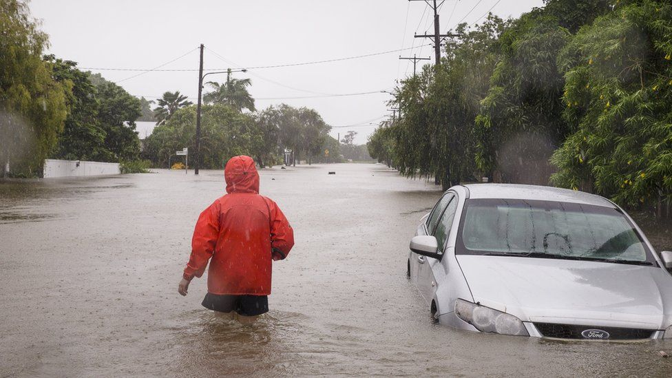 A man wades through flood water up to his thighs in Townsville
