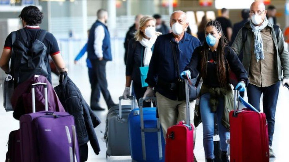 Passengers wear protective masks as they arrive at Frankfurt airport on Tuesday