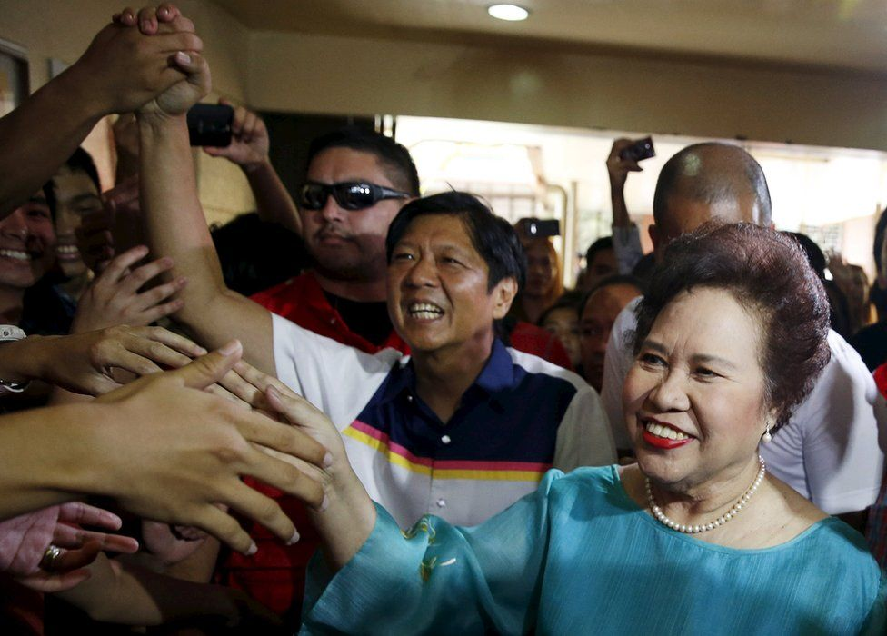 """Philippine presidential candidate Miriam Santiago and running mate vice presidential candidate Ferdinand """"Bongbong"""" Marcos (C) greet supporters during an election campaign for the May 9 election, in the mountain resort of Baguio city in northern Philippines 16 April 2016"""