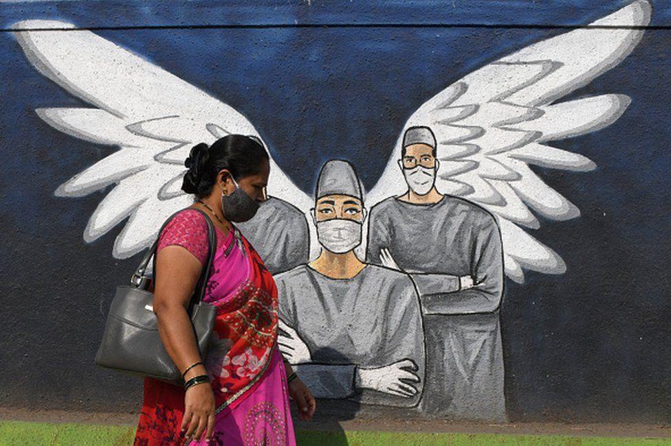 A woman wearing a face mask walks past a graffiti painted to create awareness about the coronavirus disease. Graffiti, besides creating awareness about coronavirus pandemic, it is painted to beautify the walls in Vashi (a suburb in Navi Mumbai).