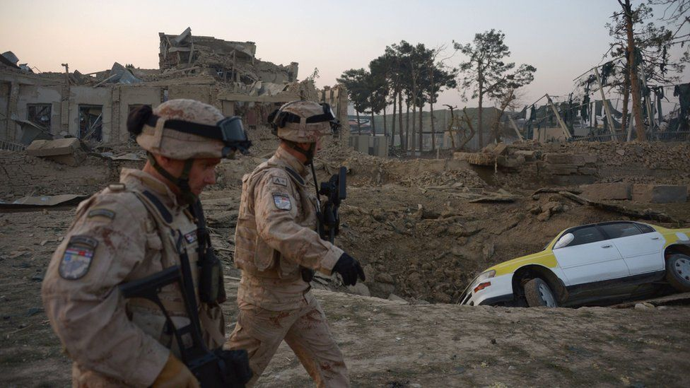 Croatian soldiers from the NATO coalition are walking past a crater from a bomb blast as they inspect the site of an attack targeting the German consulate in Mazar-i-Sharif on November 11, 2016.