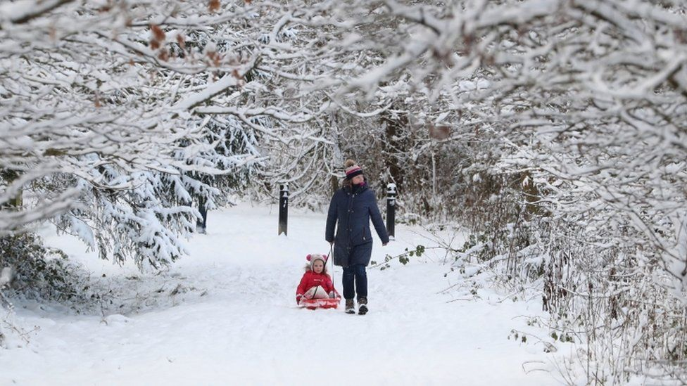 A woman tows a child on a sledge through a snow-covered wood at Larbert, near Falkirk in Scotland