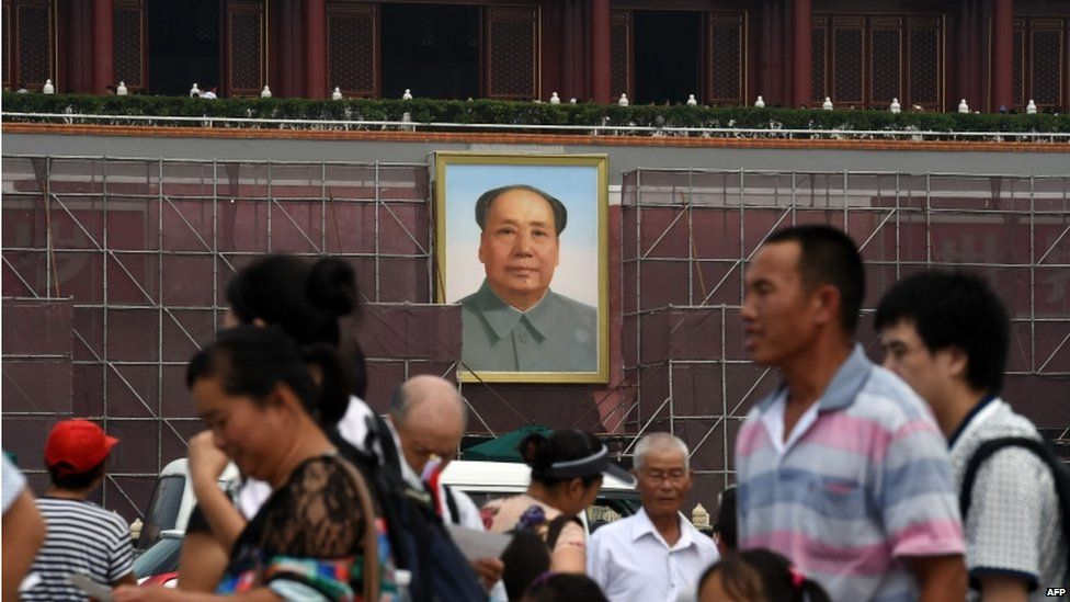 Tourists walk in Tiananmen Square in front of scaffolding next to the portrait of late communist leader Mao Zedong on Tiananmen rostrum in Beijing on 23 July 2015.