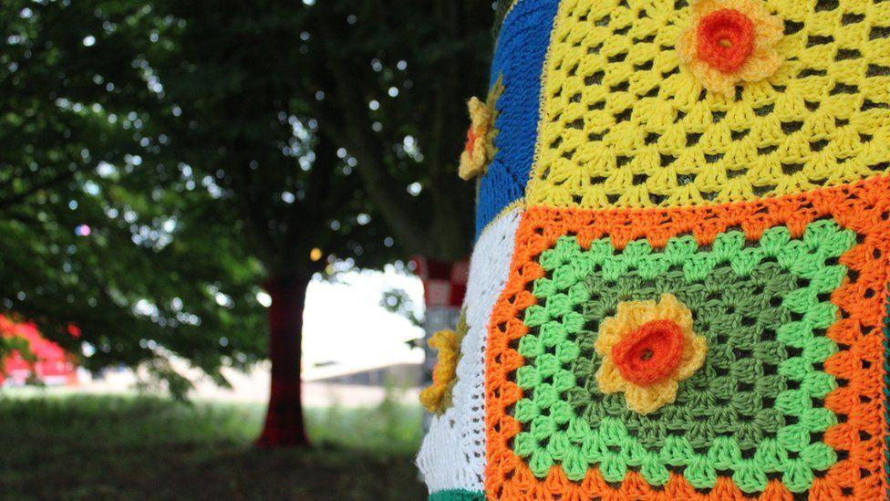 Y coed yn eu cotiau amryliw // A yarn bombing display brings colour to a shady glade