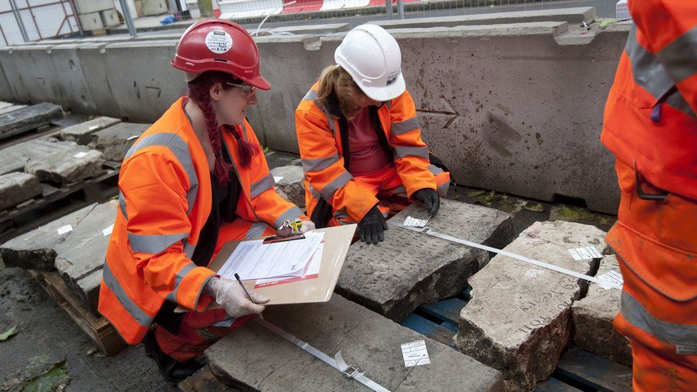 Volunteers in London recording a gravestone before it is removed ahead of the construction of HS2.