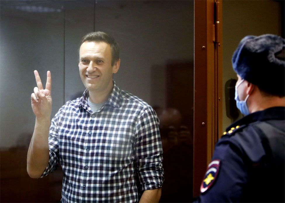 Alexei Navalny makes a V sign with his fingers as he stands in court