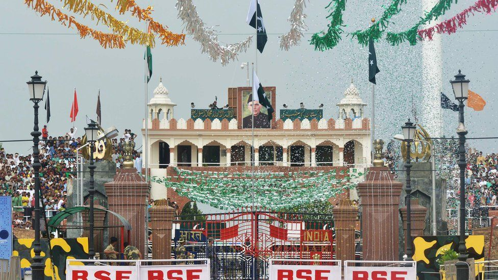 A Pakistani Ranger (top) unfurls the Pakistani national flag as Pakistani people (R/L) watch during a ceremony to celebrate Pakistan's Independence Day at the India-Pakistan Wagah border post on 14 August 2017