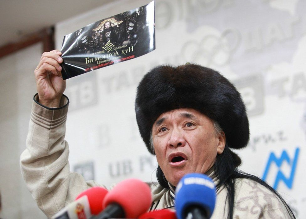Sevjidiin Sukhbaatar, the father of injured Mongolian rapper Amarmandakh Sukhbaatar, holds up a poster featuring a swastika symbol at a press conference about his son in Ulan Bator, Mongolia, on December 2, 2016.