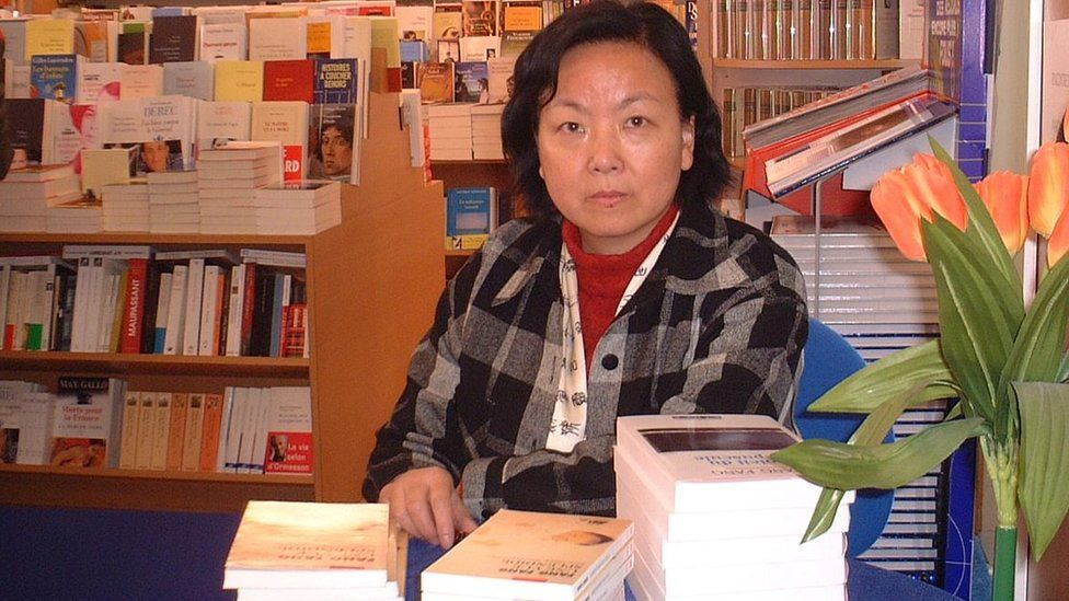 Fang Fang at a book signing in a bookshop.
