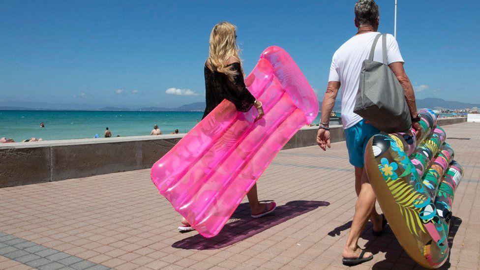 Tourists walk holding inflatable mattress at Palma Beach in Palma de Mallorca on June 7, 2021.