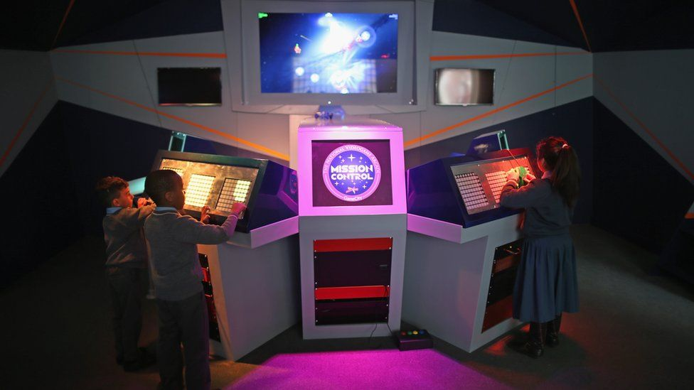Children play on Mission Control in the National Videogame Arcade