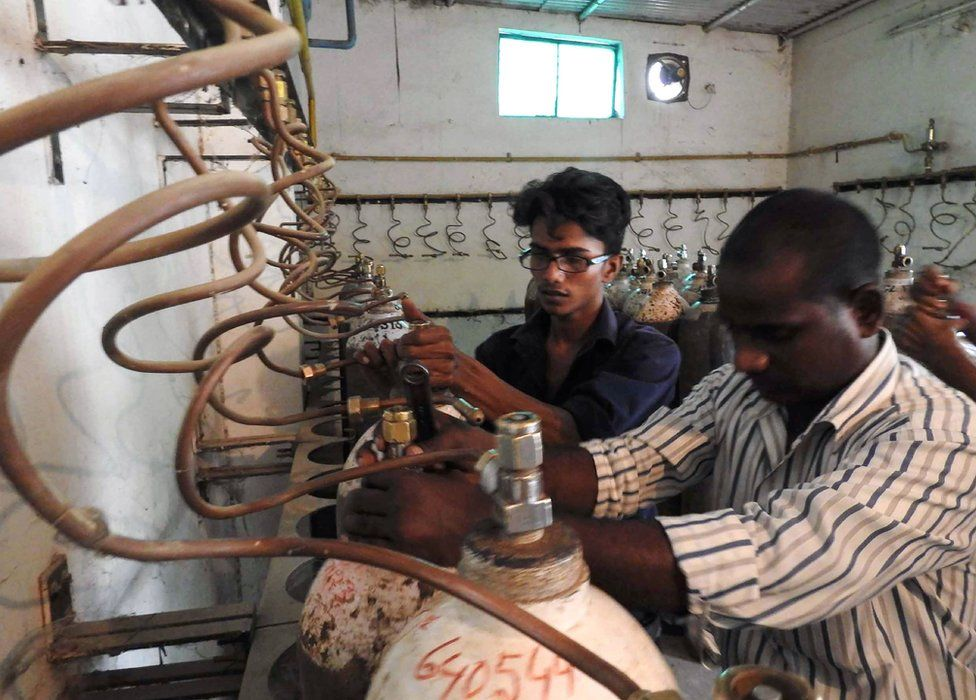 Workers examining oxygen cylinders at the hospital