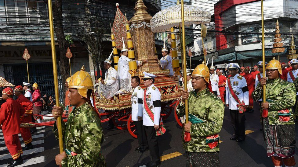 Men in ceremonial uniforms walk in a procession transporting the royal urn containing the remains of Thailand's most senior Buddhist monk, the late Supreme Patriarch Somdet Phra Nyanasamvara