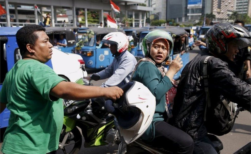 A man hits a motorbike taxi driver in Jakarta
