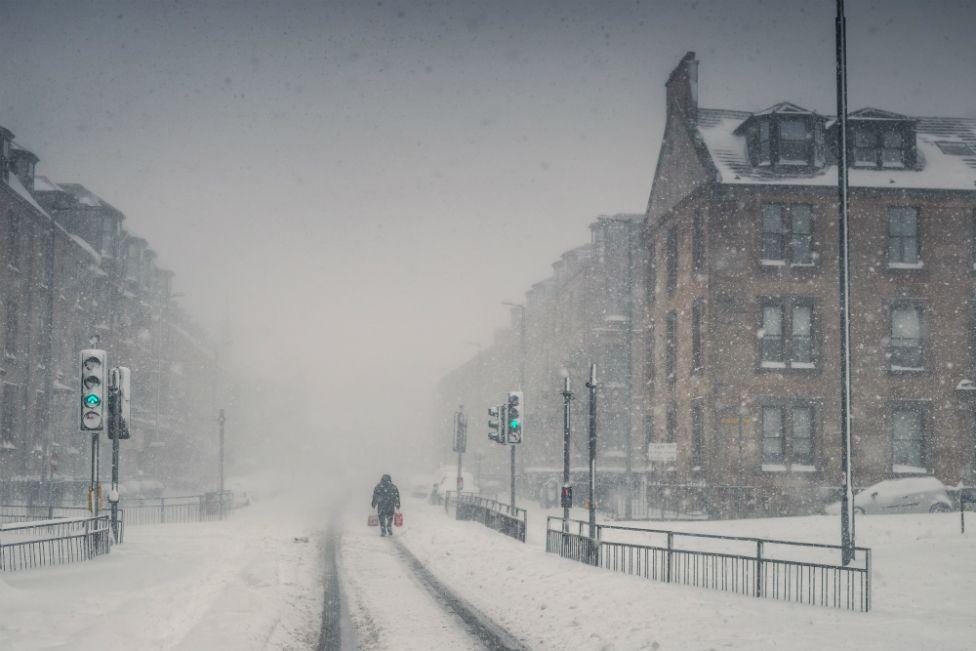 A lone figure walks through a blizzard