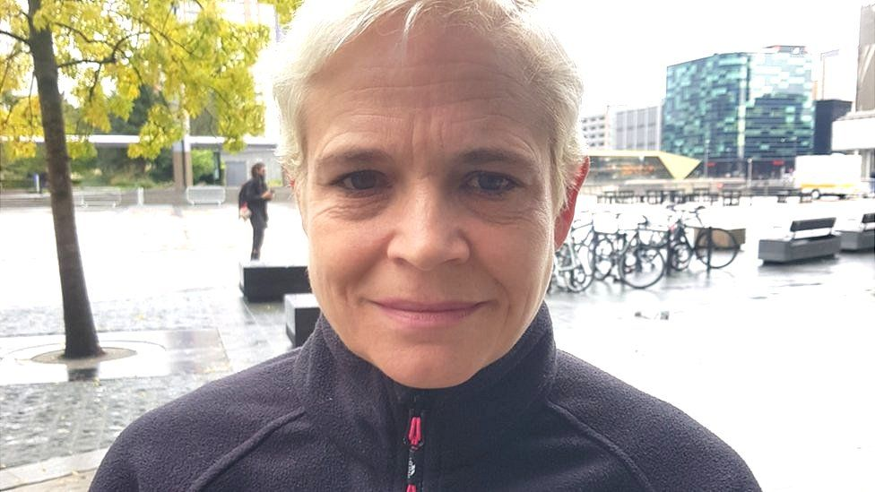 A head and shoulders shot of a woman with short, dyed white hair and a black fleece top standing outside in front of modern glass buildings and a bicycle rack.