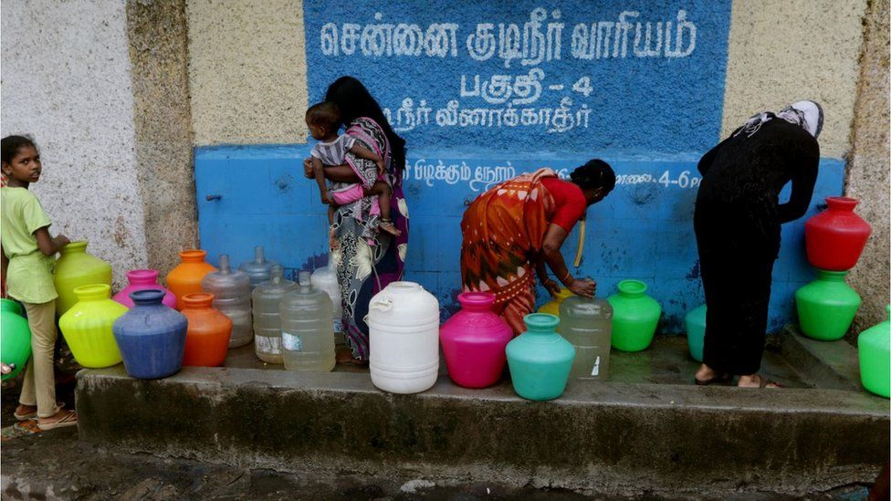 Indian residents stand around with plastic pots filled with drinking water at a distribution point in Chennai on June 20, 2019. - Water levels in the four main reservoirs in Chennai have fallen to one of its lowest levels in 70 years, according to Indian media reports