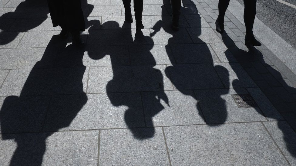 Shadows of people walking on a pavement