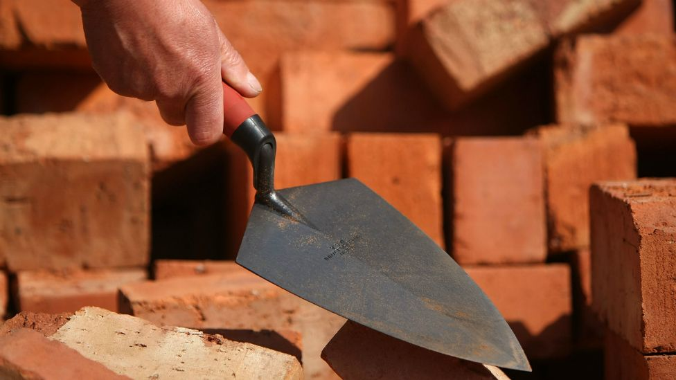 A brick layer's trowel in front of a pile of bricks