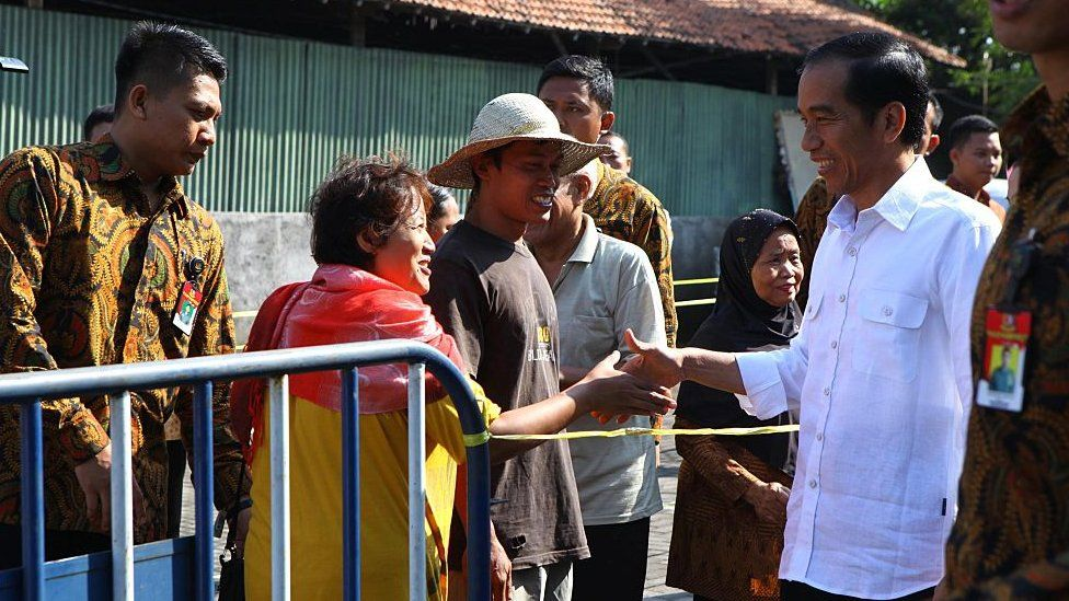Indonesian President Joko Widodo gives money and food packages to poor people during Eid al Fitr celebration in Surakarta,