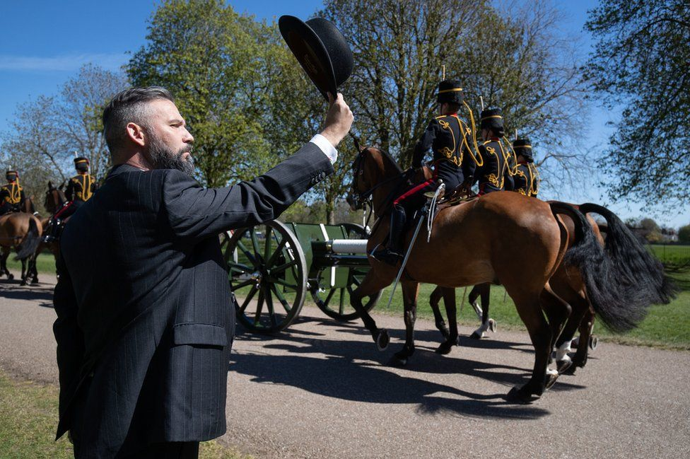 A person salutes the King's Troop Royal Horse Artillery as they make their way down the Long Walk towards Windsor Castle, as the funeral of the Duke of Edinburgh takes place in St George's Chapel, at Windsor Castle, Berkshire