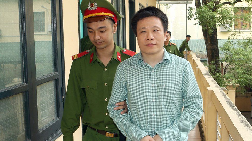 Image shows Ha Van Tham being led to court