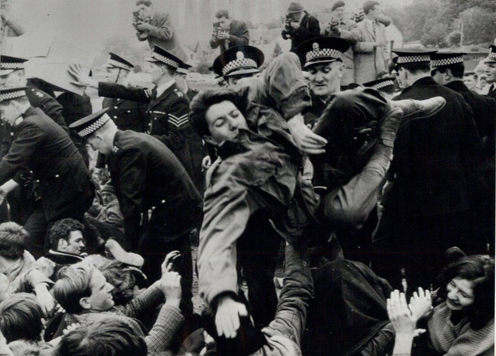 May 22, 1961 - New Clashes At The Holy Loch: There were more incidents at Holy Loch to-day as the remaining anti-polaris demonstrators continued to make their protests. Three American officers, were involved in one incident with the demonstrators as the officers tried to board Proteus. The officer arrived in a car at Ardadam Pier, the embarkation point for their ship, to find 60 people on a sit-down vigil outside the locked pier gates. The officer, had to tramp over shoulders, legs and feet, amid cries of pain, to get to the gates. The protectors offered no other resistance - Image ID: E0W3G4