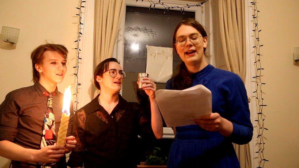Three Jewish people performing havdalah in a living room