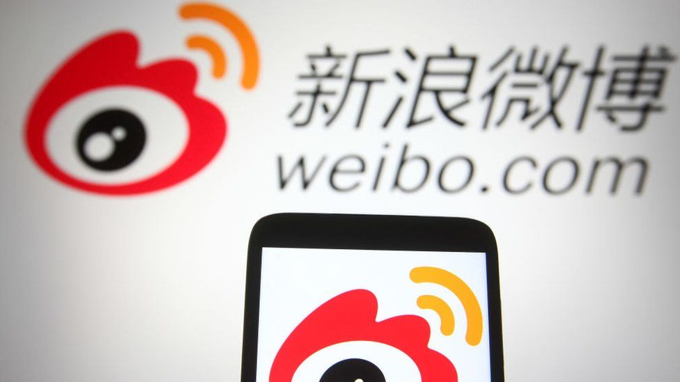 Weibo (Sina Weibo) logo of a Chinese social media platform is seen on a smartphone and a pc screen.