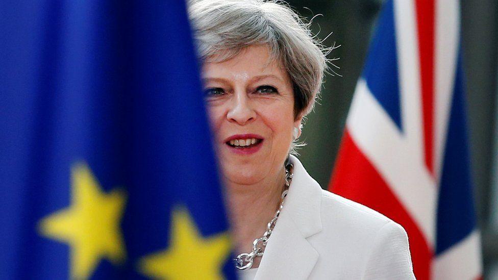 Theresa May next to EU ad UK flag