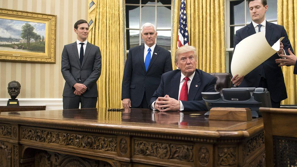 President Donald Trump prepares to sign a confirmation for Defense Secretary James Mattis in the Oval Office