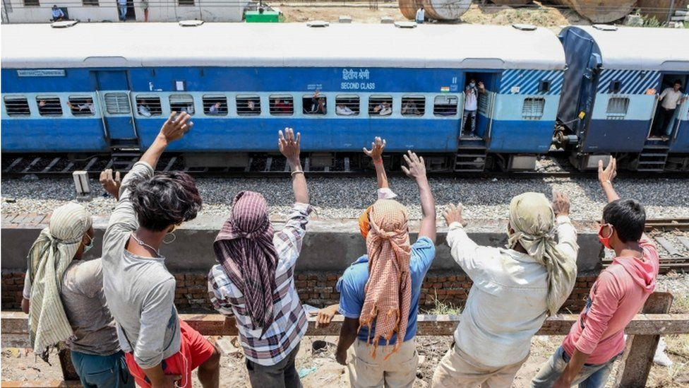 Labourers standing on a roadside wave to migrant workers and families sitting in a special train from Amritsar to Barauni of Bihar state as they go back to their hometowns May 10, 2020 after the government eased a nationwide lockdown