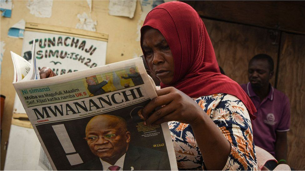 A woman reads a newspaper announcing the death of Tanzania's President John Magufuli in Dar es Salaam, on March 18, 2021.