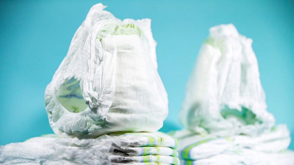 A stock photo shows unused disposable nappies in a stack against a blue background