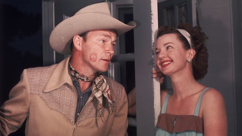 Dale Evans (1912 - 2001) smiles after leaving a red lipstick mark on the cheek of her husband, American singer and actor Roy Rogers (1911 - 1998), upon his arrival through the front door