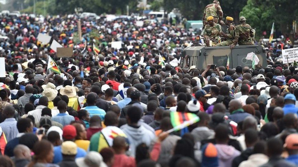 People march past an armoured personnel carrier in Harare (18 November 2017)
