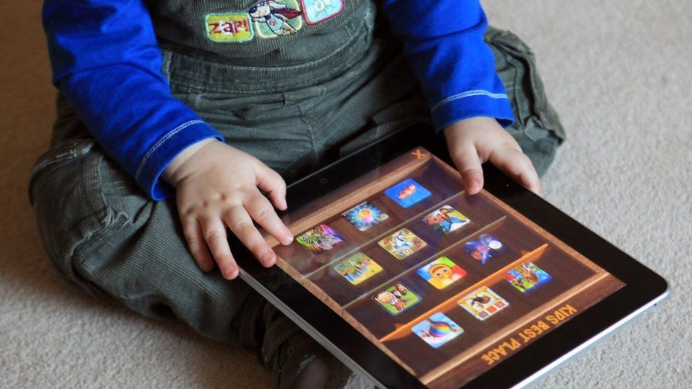 A toddler uses an iPad at his home