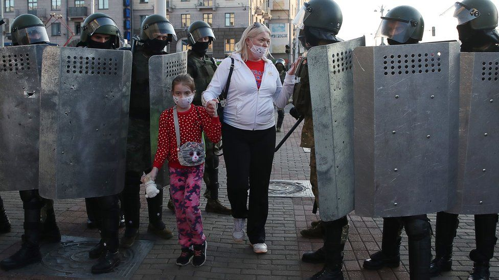 A woman with a child talks to riot police officers blocking an area during a rally in Independence Avenue on 20 September