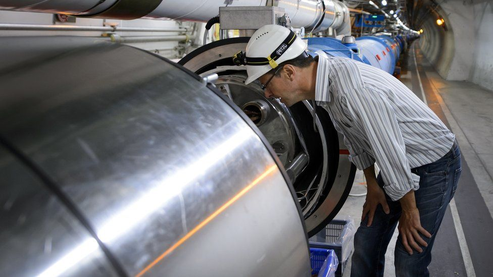 A scientist looks at a section of the European Organisation for Nuclear Research (CERN) Large Hadron Collider (LHC), during maintenance works on July 19, 2013 in Meyrin, near Geneva