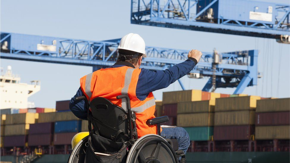 Transportation engineer in a wheelchair giving directions to shipping containers at shipping port