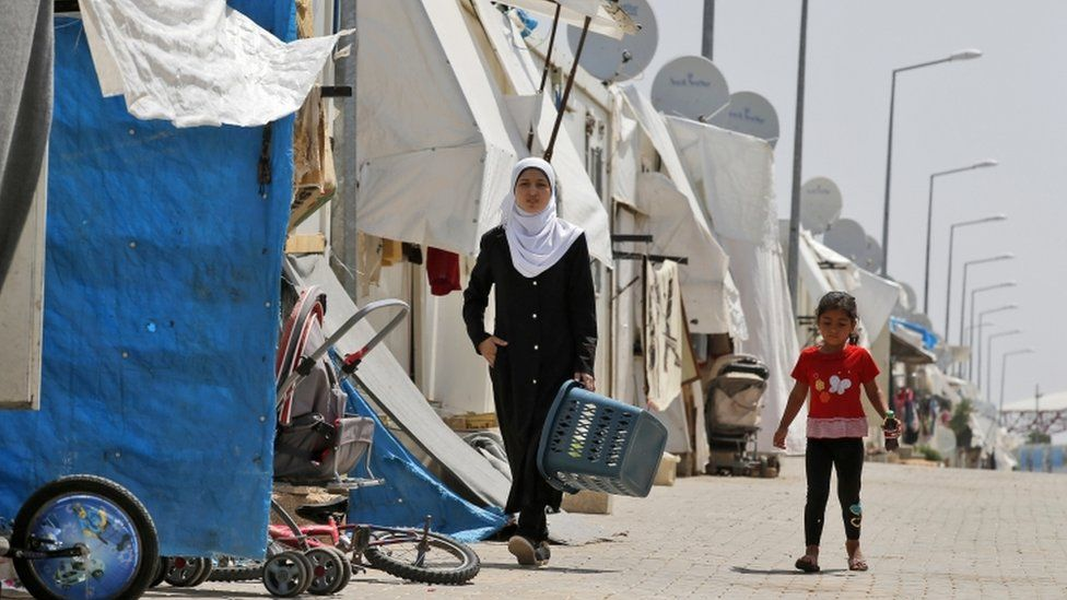 Syrian refugees walk at the Oncupinar camp for Syrian refugees next to the border crossing with Syria, near the town of Kilis in south-eastern Turkey