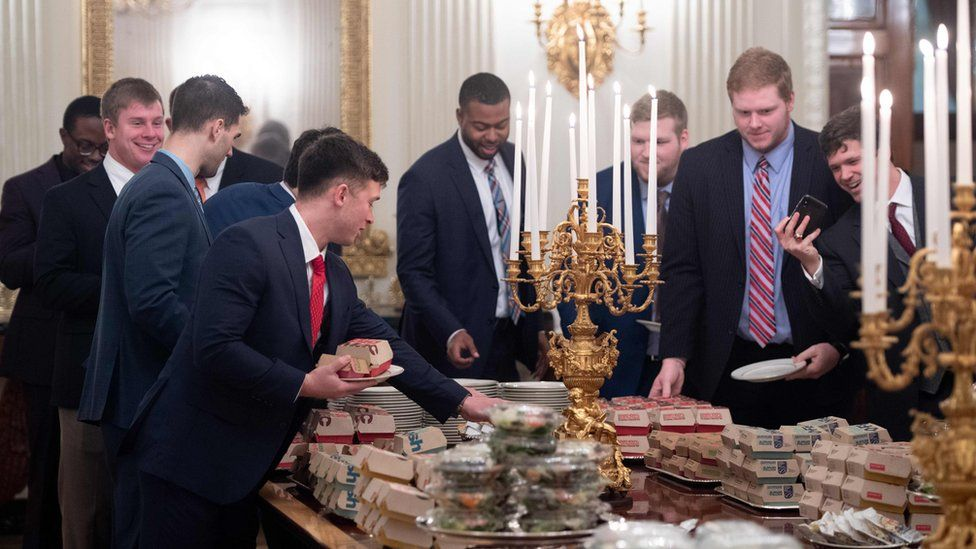 Guests select fast food that the US president purchased for a ceremony honouring the 2018 College Football Playoff National Champion Clemson Tigers