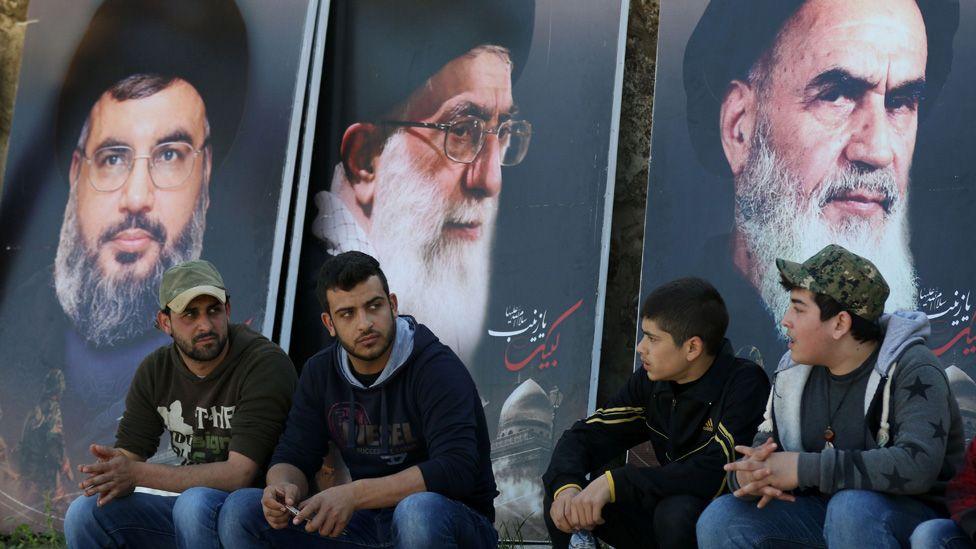 Lebanese sit in front of giant posters bearing portraits of Hassan Nasrallah, the head of Lebanon's militant Shiite Muslim movement Hezbollah (L), the founder of Iran's Islamic Republic, Ayatollah Ruhollah Khomeini (R) and Iran's supreme leader Ayatollah Ali Khamenei (C) during the funeral of a Hezbollah fighter