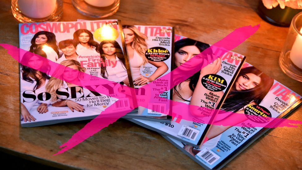 Table display of Cosmopolitan magazines with a large pink cross over them