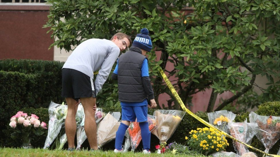 Residents bring flowers to a makeshift memorial at the Tree of Life synagogue
