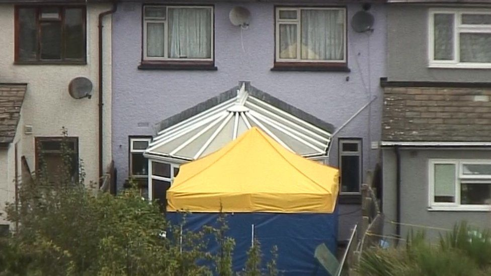 a forensic tent in the back garden of property being searched in Sunbury-on-Thames